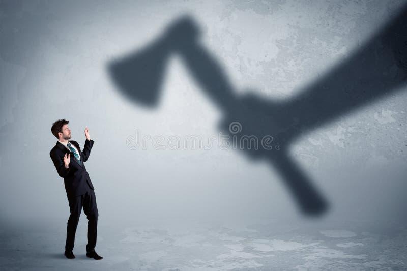 Homme d'affaires effrayé d'une main énorme d'ombre tenant un concept de hache illustration stock