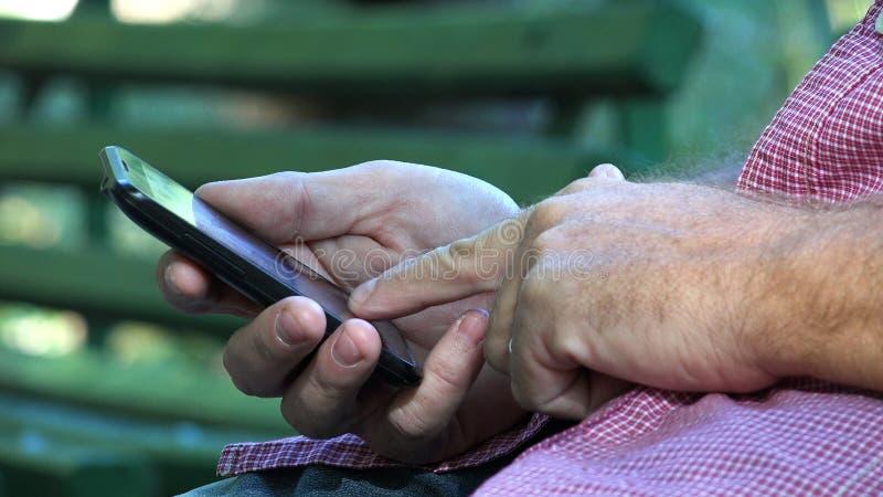 Homme d'affaires en parc se reposant sur le texte de banc utilisant le réseau sans fil de téléphone portable photographie stock libre de droits