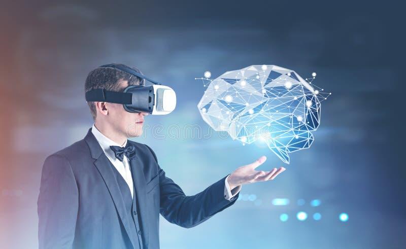 Homme d'affaires en verres de VR montrant un hologramme de cerveau photo stock