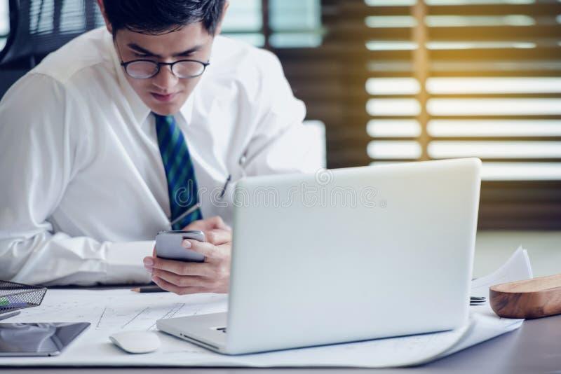 Homme d'affaires en verres se reposant au bureau utilisant le téléphone portable photographie stock libre de droits