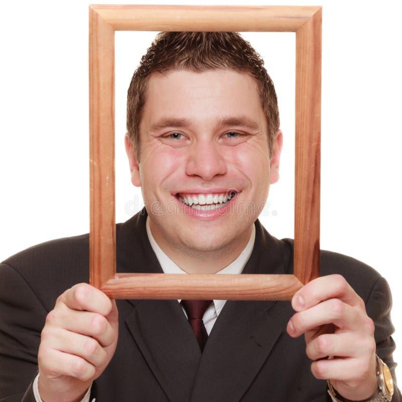 Homme d'affaires encadrant son visage avec le cadre en bois photographie stock libre de droits