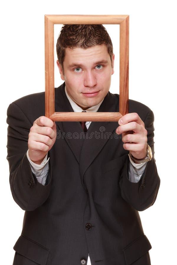 Homme d'affaires encadrant son visage avec le cadre en bois image stock