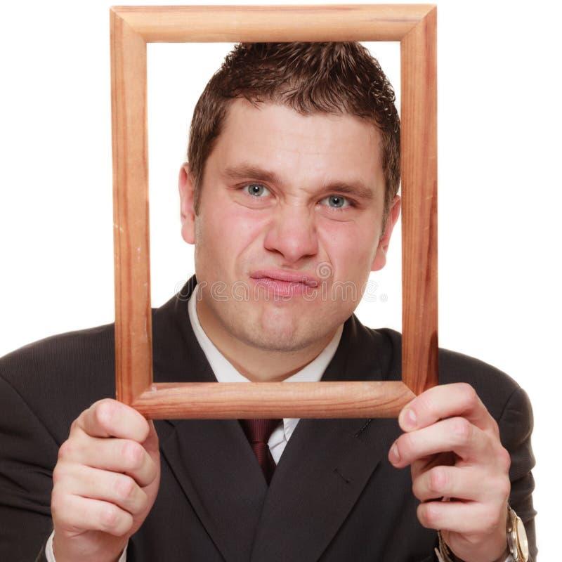 Homme d'affaires encadrant son visage avec le cadre en bois images libres de droits