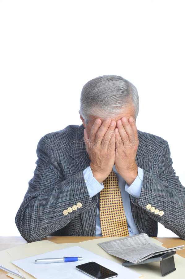 Homme d'affaires enfoncé à son bureau avec le visage dans des mains image libre de droits