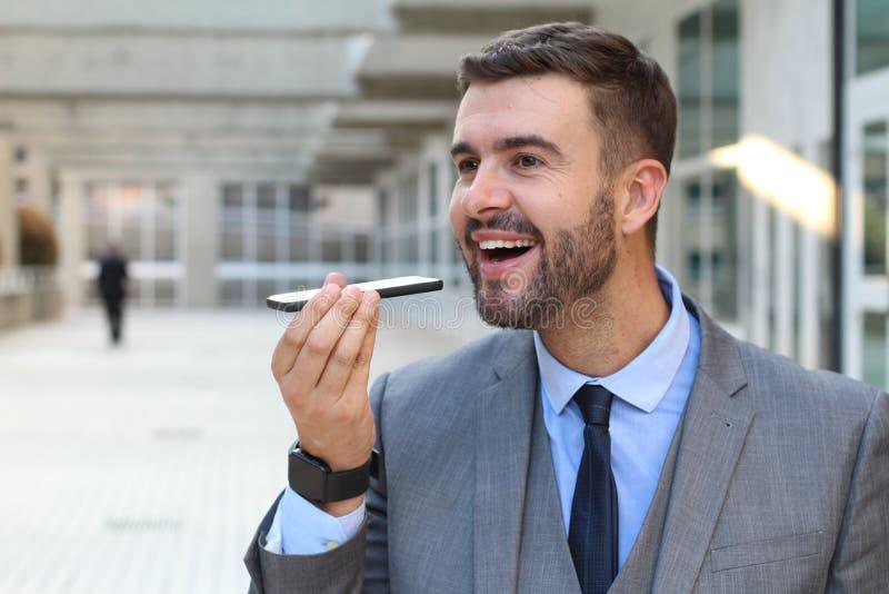 Homme d'affaires enregistrant le message audio dans des bureaux photographie stock