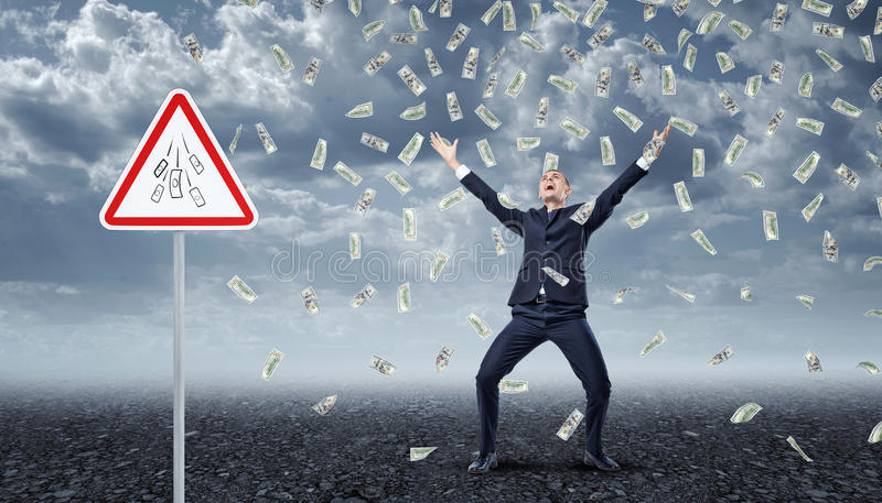 Homme d'affaires enthousiaste se tenant sous beaucoup de billets d'un dollar tombant du ciel avec un ` d'argent de ` de panneau d photographie stock libre de droits