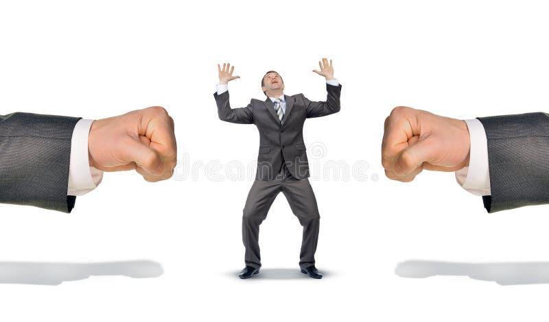 Homme d'affaires entre deux grands poings image stock