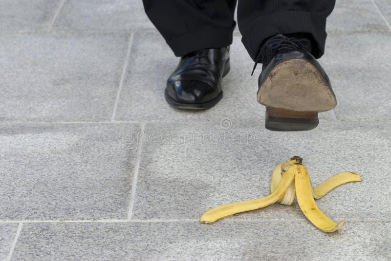 Homme d'affaires environ à l'étape sur une peau de banane image stock