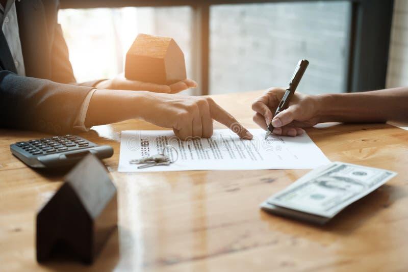 Homme d'affaires et agent immobilier signant un document pour l'affaire de maison, image stock