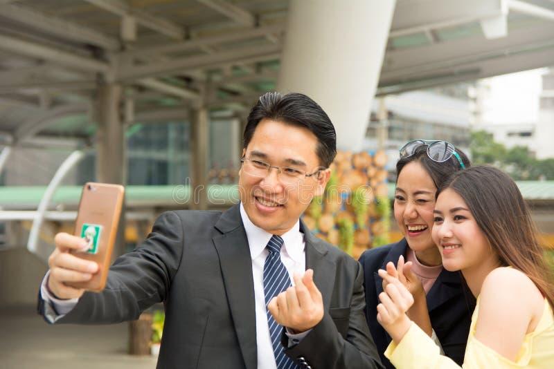 Homme d'affaires et dames prenant des photoes de selfie avec le mini coeur photos stock