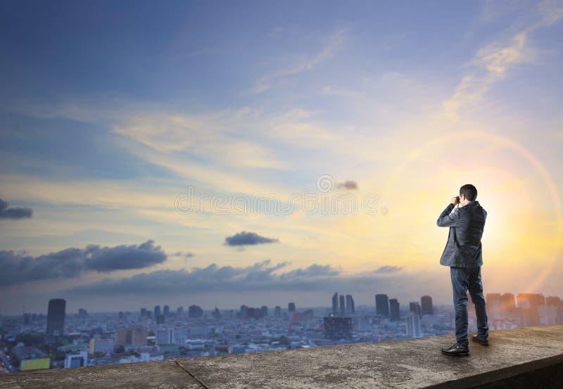 Homme d'affaires et espionnage binoculaire sur le bâtiment avec urbain photos stock