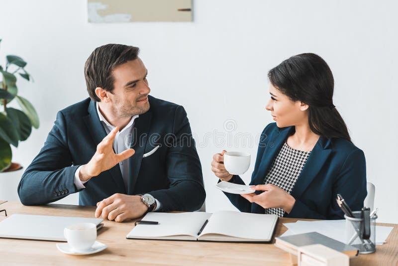 Homme d'affaires et femme d'affaires ayant une discussion au sujet du projet photographie stock libre de droits