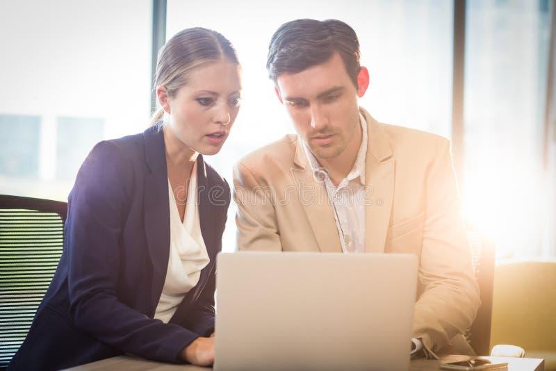 Homme d'affaires et femme d'affaires agissant l'un sur l'autre utilisant l'ordinateur portable images libres de droits