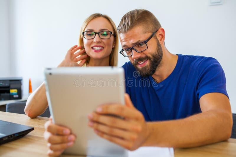 Homme d'affaires et femme d'affaires analysant des diagrammes sur le PC de comprimé off images stock