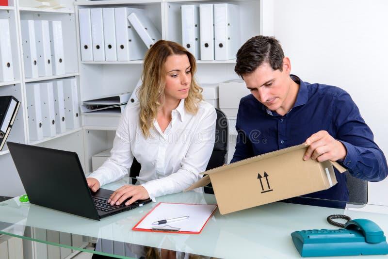 Homme d'affaires et femme d'affaires avec la livraison dans le bureau photo stock