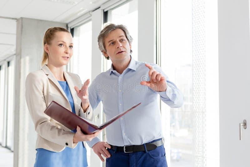Homme d'affaires et femme d'affaires avec le dossier ayant la discussion dans le bureau photo libre de droits
