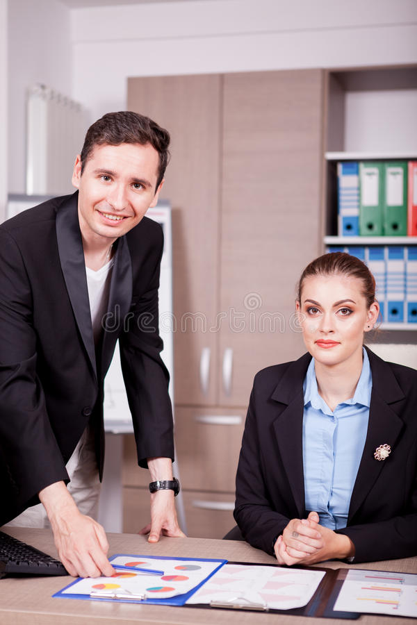 Homme d'affaires et femme d'affaires dans le bureau avec des diagrammes sur la table photos stock