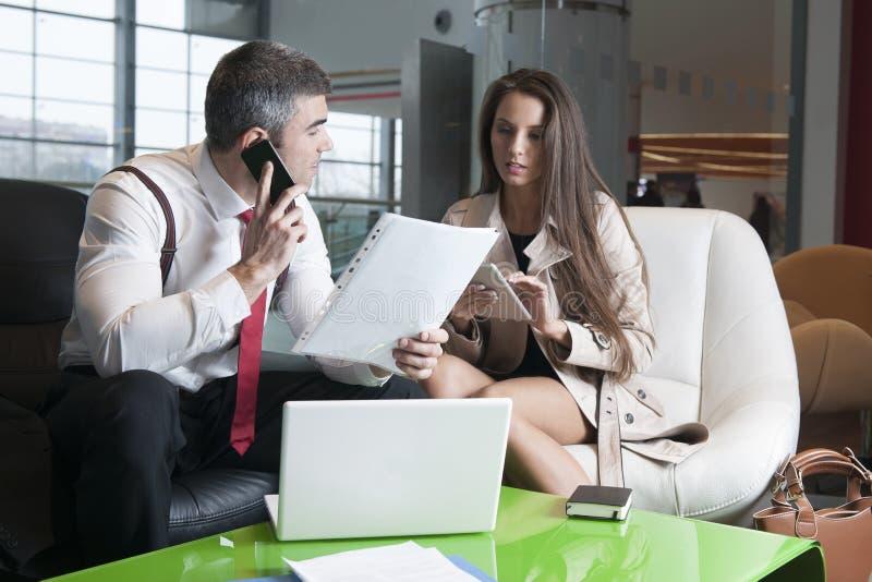 Homme d'affaires et femme d'affaires lors de la réunion avec l'ordinateur portable et le comprimé photos libres de droits