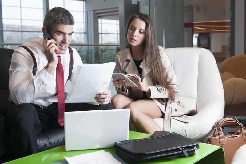 Homme d'affaires et femme d'affaires lors de la réunion avec l'ordinateur portable et le comprimé photographie stock
