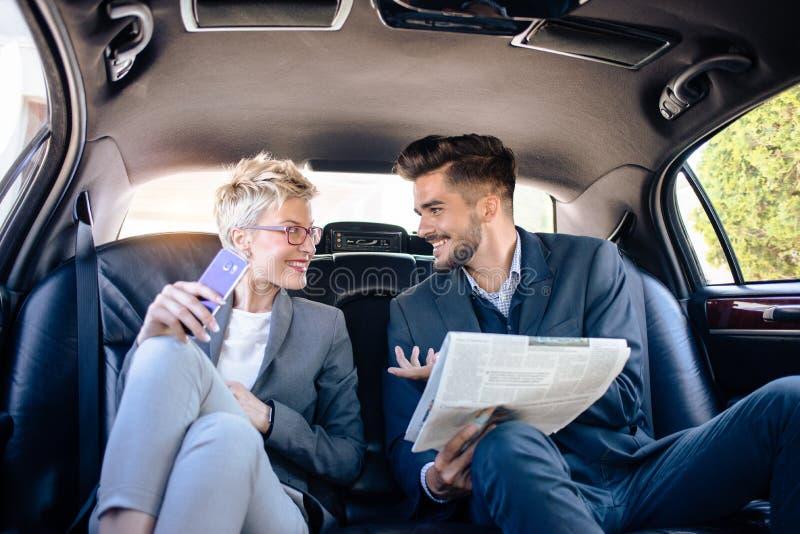 Homme d'affaires et femme d'affaires parlant dans la limousine photos stock
