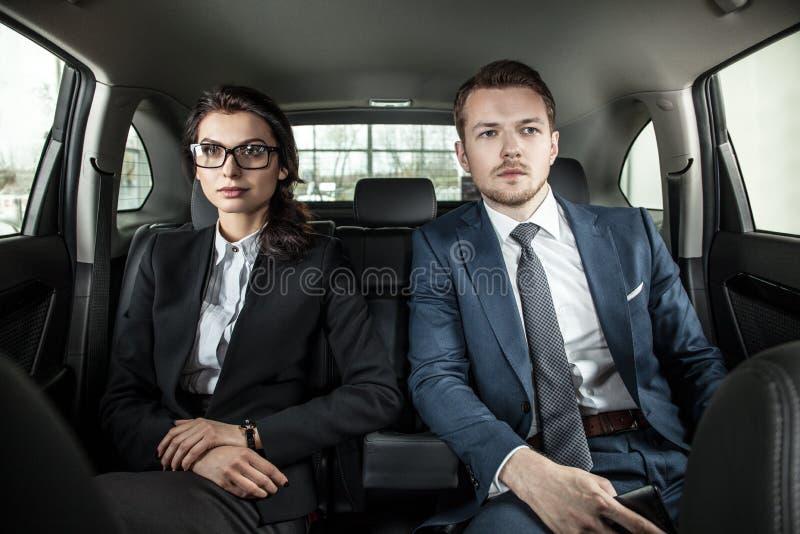 Homme d'affaires et femme d'affaires s'asseyant dans une limousine photo stock