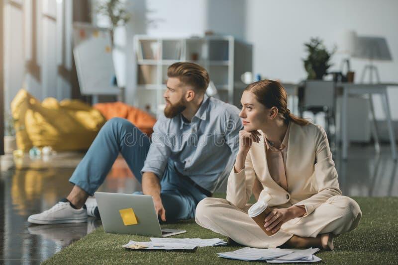 Homme d'affaires et femme d'affaires s'asseyant sur le plancher et à l'aide de l'ordinateur portable photographie stock