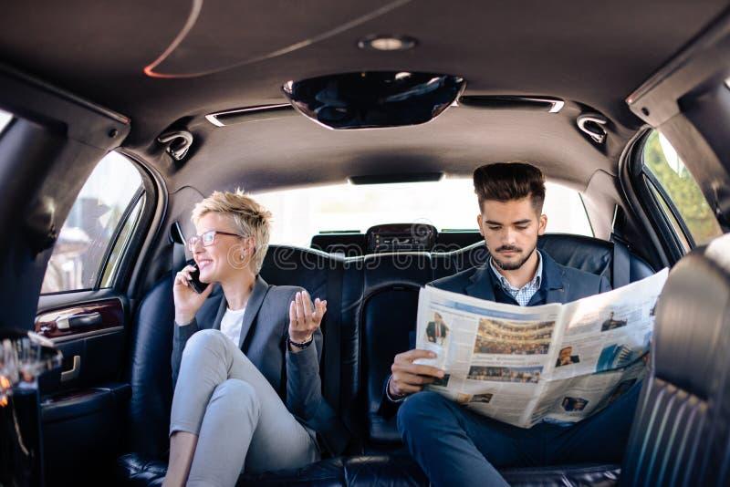 Homme d'affaires et femme d'affaires dans la limousine photos stock