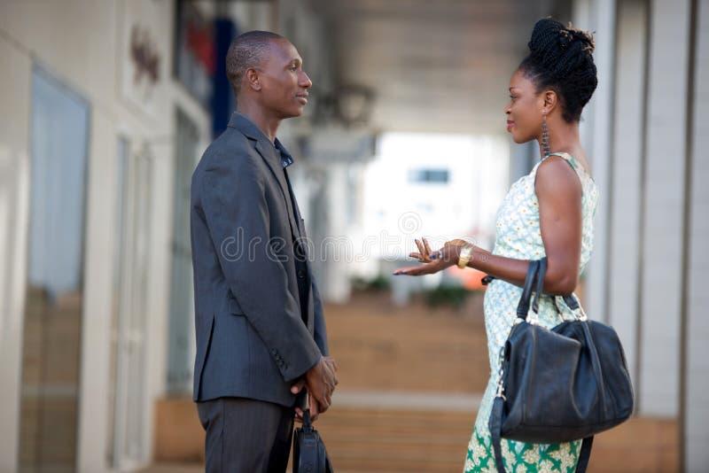 Homme d'affaires et femme d'affaires discutant le travail se tenant face à face images stock