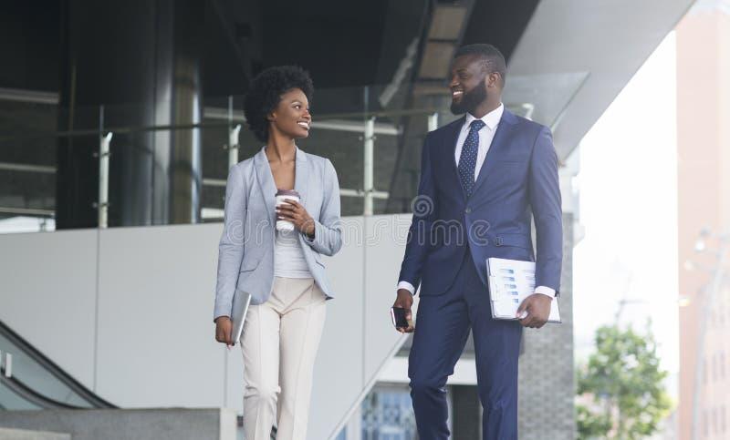 Homme d'affaires et femme d'affaires discutant le travail tout en marchant l'extérieur photographie stock libre de droits