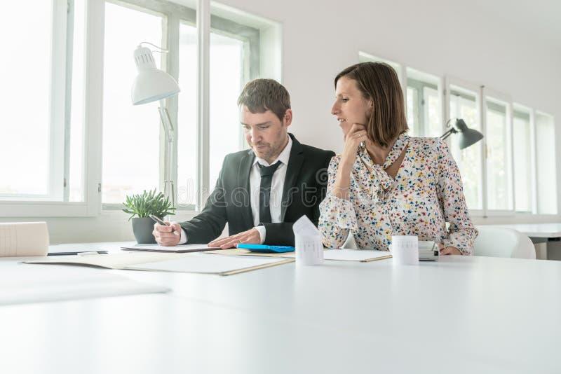 Homme d'affaires et femme d'affaires faisant des calculs et écrivant pas photos libres de droits