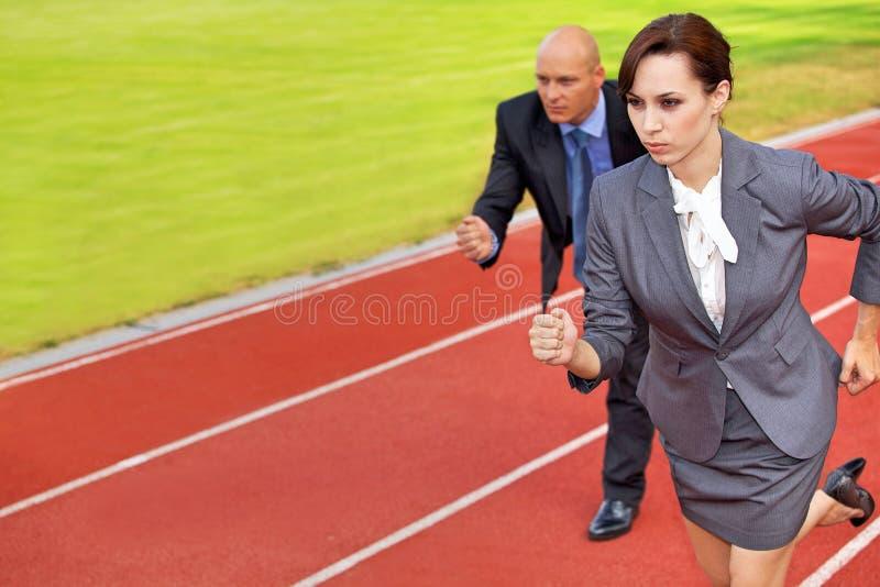 Homme d'affaires et femme sur courir sur la voie de course images stock