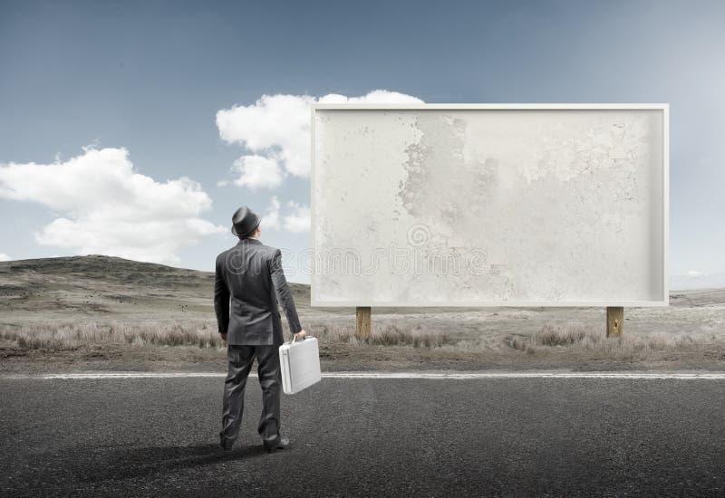 Homme d'affaires et vieux panneau d'affichage vide images stock