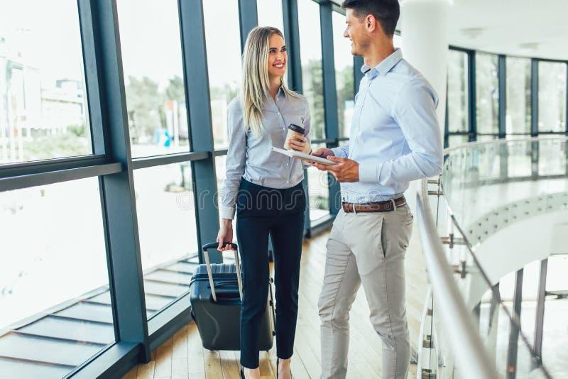 Homme d'affaires et voyage parlant de bagage de sourire et de prise de femme d'affaires au voyage d'affaires image stock