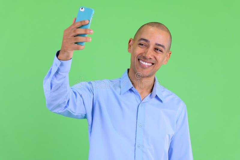 Homme d'affaires ethnique multi chauve heureux prenant le selfie images stock