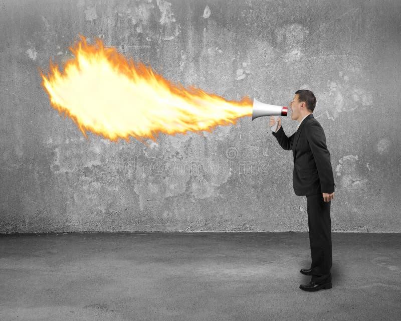 Homme d'affaires fâché criant dans le feu de crachement de mégaphone avec la Co photographie stock