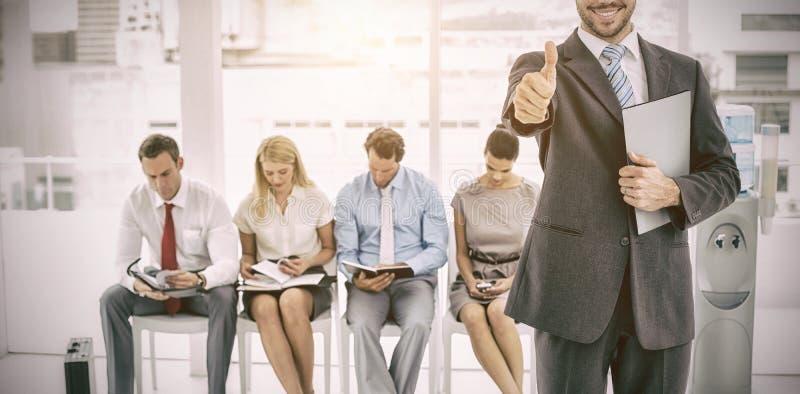 Homme d'affaires faisant des gestes des pouces contre l'entrevue de attente de personnes image libre de droits
