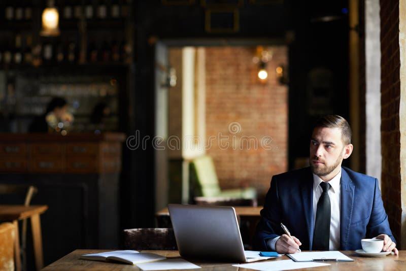Homme d'affaires faisant des notes dans le rapport photographie stock