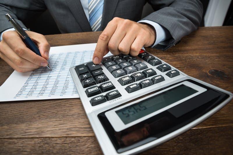 Homme d'affaires faisant le calcul dans le bureau photographie stock