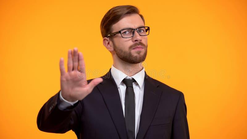 Homme d'affaires faisant le geste d'arr?t, rejetant pour se surmener, fond orange image libre de droits