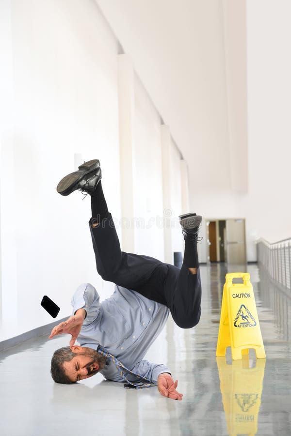 Homme d'affaires Falling sur le plancher humide image stock