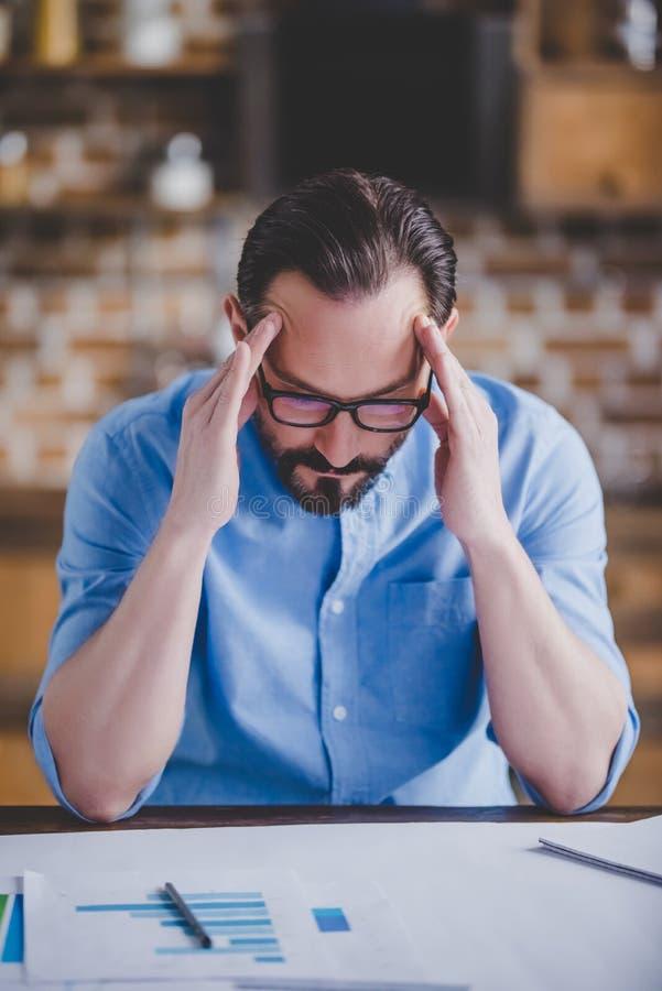 Homme d'affaires fatigué avec la migraine après travail photo stock