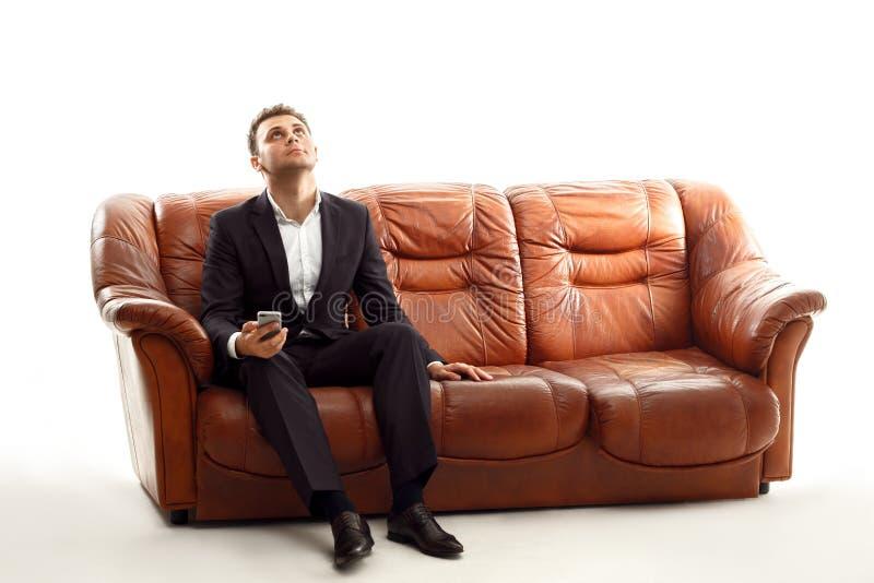 Homme d'affaires fatigué avec le téléphone se reposant sur le sofa recherchant photographie stock