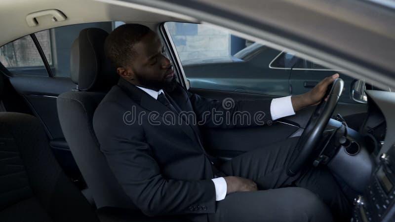 Homme d'affaires fatigué bouleversé s'asseyant dans la voiture, pensant à la dissolution, problèmes images libres de droits