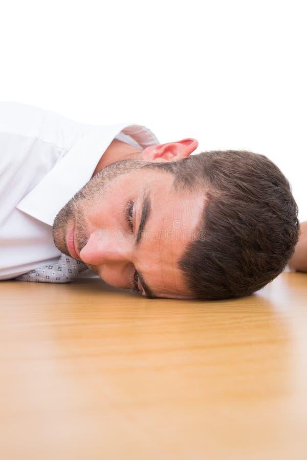 Homme d'affaires fatigué se reposant sur son bureau photographie stock