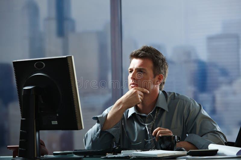 Homme d'affaires travaillant tard dans le bureau photos stock