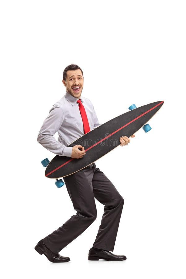 Homme d'affaires feignant pour jouer la guitare sur un longboard images libres de droits