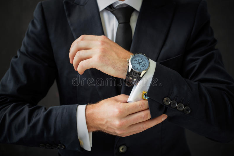 Homme d'affaires fixant son costume photos stock
