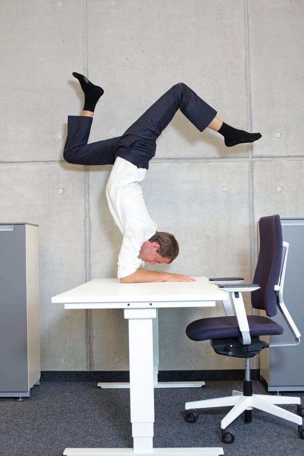 Homme d'affaires flexible en asana de scorpion sur bureau réglable en hauteur électrique image libre de droits