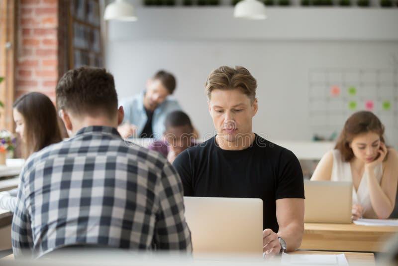 Homme d'affaires focalisé sérieux travaillant sur l'ordinateur portable dans la Co-wor images stock