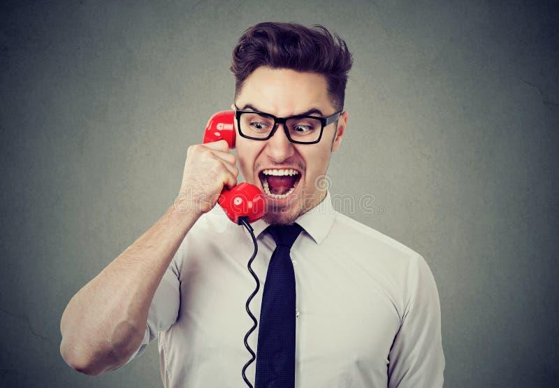 Homme d'affaires fol fâché criant au téléphone image stock